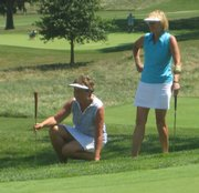 Lawrence's Janet Magnuson, left, and Michele Johnson read a putt on the 12th green. The two played Wednesday at Lawrence Country Club in the Tee-Fore-Two tournament.