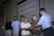 J.R. Condra, at right, of Cottonwood Industries, presents Carolyn Palka, third from right, with a plaque recognizing her work for the company, which earned PackerWare's Vendor of the Quarter Award. Cottonwood was honored Thursday at PackerWare's plant, 2330 Packer Road. Also representing Cottonwood were, from left, Steve Steinbach, James Herron, Sharon Spratt and Glenda Shelby, second from right.