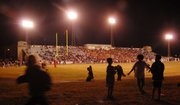 Children play a game of touch football as Lawrence High plays Free State at Haskell Stadium in this file photo.