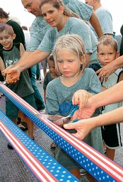 Gracie Folks, 6, and Andine Robbins, of Perry, help at the Perry-Lecompton ribbon-cutting ceremony Friday to celebrate the reopening of the Kansas River bridge that links the two communities. The bridge had been closed for about five months.
