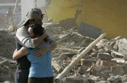 Residents embrace each other friday in front of a house destroyed by the earthquake that shook southern Peru, in Pisco. A powerful magnitude-8 quake that devastated the southern coast of Peru on Wednesday killed at least 510 people and 1,500 were injured, authorities said.
