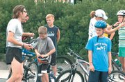 Dustin Morris, left, instructs participants of the Alive with MissionMe triathlon clinic on helmet safety. Nine youngsters attended Sunday's clinic at the Lawrence Indoor Aquatic Center.