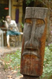 "Ed and Bonnie Schmiedeler&squot;s home and garden are full of recycled finds - a visual depiction of the adage ""one man&squot;s trash is another man&squot;s treasure."" They call this wooden head Ken-Tiki because it was carved by an artist friend named Ken. In the background, the couple&squot;s roving mannequin rests on a chair, dressed for summer and staring into a backyard full of miscellanea."