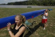 Kansas University Sophomore crew team members Julie Schoeneck, New Berlin, Wis., left, and Kerri Emel, Hutchinson, return a boat to storage Monday after cleaning the equipment in Burcham Park near the Kansas River.