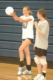 west freshman volleyball player Emma Cormack, left, practices a serve as teammate Victoria Gilman looks on.