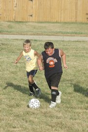 Bryce Hadl, left, and Caden Barnett fight for the soccer ball during their practice Tuesday at Southwest Junior High. Both play for the Fireball Dragons recreation team, which is part of the Kaw Valley Soccer Association. The KVSA club and recreation season starts Saturday at Youth Sports Inc.