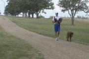 Reigning Big 12 cross country champion Colby Wissel goes for a stroll with Molly (on leash) and Forest on the Haskell Indian Nations University campus. Wissel and the pooches go for a daily jog unless it's too hot, and the jog becomes a walk. Forest sometimes pants his way to a ride.