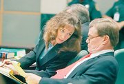 Former astronaut Lisa Nowak, left, talks with one of her attorneys, Donald Lykkebak, on Friday in the courtroom during a hearing at the Orange County courthouse in Orlando, Fla. Nowak, accused of attacking a romantic rival, asked a judge to let her remove her electronic monitoring ankle bracelet.