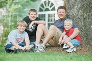 Tom Davis sits with his children, from left, Matthew, 12, Jacob, 13, and Ethan, 6, in Chatham, Va. Davis lost his wife, Elizabeth, in 2000, after she gave birth to Ethan. U.S. women are dying from childbirth at the highest rate in decades, new government figures show.