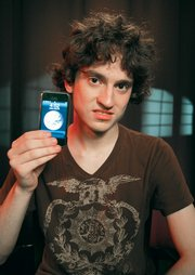 George Hotz, 17, holds an iPhone that he has unlocked and is using on T-Mobile's network, Friday in New York. Hotz has broken the lock that ties the iPhone to AT&T's network, freeing the cell phone for use on other networks.