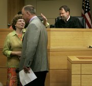 Toby Young, left, gives her attorney, Jim Yoakum, a hug after being sentenced Wednesday, July 11, 2006, in Leavenworth. Young was given 21 months in prison for her role in helping a convicted murderer escape from the Lansing Correctional Facility in a dog crate.