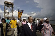 Norwood Thompson, center, joins hands with Douglas Haywood, right, as they walk with other marchers down the bridge over the Industrial Canal on the second anniversary of Hurricane Katrina in the Lower Ninth Ward of New Orleans. The marchers protested the slow pace of recovery from the storm.