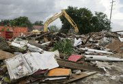 An excavator works to clear the debris of a hurricane-damaged home Wednesday in the Lakeview section of New Orleans. Two years after Katrina, large sections of the city still lie in ruins.
