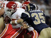 Kansas City running back Larry Johnson, left, runs past St. Louis safety Todd Johnson on his way to a seven-yard gain. Johnson returned to the football field Thursday for the first time since his holdout.