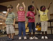 Children from the East Heights Early Childhood Center sing a song Friday during the Community Education Breakfast. From left are Henry Selig, Hannah Reese, and twins Elise and Amanda Ochieng.