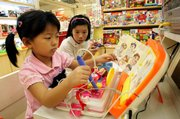 Chinese children try out toys Friday at a mall in Shanghai, China. Recall systems for unsafe food products and toys went into effect in China on Friday as part of a bid to improve product safety, state media said.
