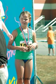 Lawrence resident Cierra Campbell, 10, holds her third-place medal at the conclusion of the IronKids triathlon Sunday at Free State High. Nearly 30 participants from Lawrence joined 150 others to compete in the event.