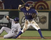 Texas second baseman Ian Kinsler, right, turns to throw to first base from second after forcing out Mark Teahen (24). The Rangers won, 9-8, Tuesday in Arlington, Texas.