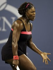 Serena Williams reacts after losing in straight sets to Justine Henin on Tuesday at the U.S. Open.