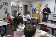 School Resource Officer Matt Sarna talks with students Wednesday at Free State High School, explaining his role at the school during a late-morning class. The city of Lawrence, which funds the student resource officers and crossing guards in the Lawrence school district, wants the district to pay for part of those costs beginning next school year.