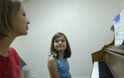 Savannah Price, 11, right, takes instruction from Lisa Enns during piano practice at Hume Music, 711 W. 23rd St. Unlike many sports, playing an instrument is an activity that a child can pursue her entire life, even if she does not become the next Van Cliburn.