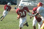 Central running back Nate Davis, left, looks for an opening in the Atchison defense during a freshman football game Thursday at Central Junior High. The Mustangs scored three unanswered touchdowns to beat Atchison, 22-8.