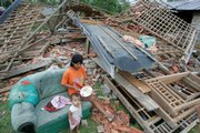A woman feeds her daughter outside her house damaged by a strong earthquake Thursday in Lais, Bengkulu, Sumatra island, Indonesia. Three powerful earthquakes jolted Indonesia in less than 24 hours, triggering tsunami warnings, damaging hundreds of houses and sending panicked residents fleeing to high ground.