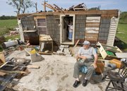 Jack Payton, 72, sits in front of his home that was severely damaged by high winds from Hurricane Humberto as his wife, Connie Payton, removes a wreath from the front door Thursday in High Island, Texas. The Paytons plan to stay with relatives until their home can be repaired. Humberto, the first hurricane to hit the United States in two years, sneaked up on south Texas and Louisiana overnight and crashed ashore Thursday with heavy rains and 80 mph winds, killing one person.