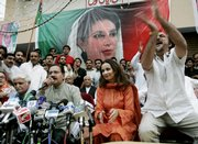 Amin Fahim, second from left, announces the return of Pakistan's former Prime Minister Benazir Bhutto on Friday in Islamabad, Pakistan. Bhutto's party announced Friday she would return from an eight-year exile to Pakistan on Oct. 18. The government said she was free to come back but would have to face corruption charges.