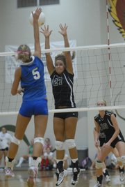 Free State's Taylor Manning, right, jumps to block a spike by a Leavenworth player. FSHS swept the Pioneers on Monday at Free State.