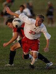 Lawrence High's Cory Wendland (23) comes away from a collision with Blue Valley West's Riley Baird. LHS fell, 7-1, on Monday at Youth Sports, inc.