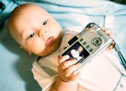 Five-month-old Jordan Short holds a camera belonging to his mother, Amy Short, whose photo is seen on the camera's screen in a posed photo at their home in East Alton, Ill. Thanks to cheap and easy-to-use recording devices - digital cameras, camcorders and camera phones - today's children are becoming the most documented generation ever.