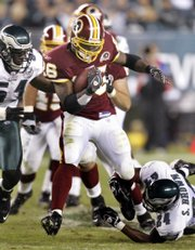 Washington's Clinton Portis, center, goes over Philadelphia Eagles' Sheldon Brown (24) in the second half. The Redskins won, 20-12, Monday in Philadelphia.