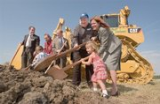 With a bulldozer as a backdrop, Jana Henry Faber (from right), two-year-old Ella Henry and Robert Henry along with other family members along with Joe Reardon (center), Mayor/CEO of Unified Government of Wyandotte County, turn over the first loads of dirt in a ground breaking ceremony Tuesday for the new Schlitterbahn Vacation Village. The Henry family, owners of three other resorts, were on hand for the first expansion outside of Texas for a $750 million year round retail entertainment and water-park destination that will be located on a 370-acre track near Village West in Kansas City, Kansas. .
