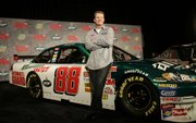 Dale Earnhardt Jr. poses with his new NASCAR race car. Earnhardt revealed his new car Wednesday in Dallas.