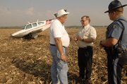 Jim Roesner, left of Salina talks to Lloyd Hetrick from the Lawrence Airport while Kansas Highway Patrol trooper J.A Kellerman listens in at the scene of a Thursday morning airplane crash. Roesner, of Salina was piloting the single-engine Beechcraft  just west of Lawrence around 8:30 a.m. when a mechanical malfunction forced him to make a hard landing in a corn field next to U.S. Highway 24-40. Roesner, the plane's only passenger, was uninjured