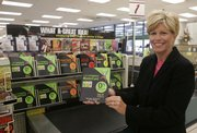 Kathy Kelly, president of Kroger Co.'s Personal Finance division, shows a credit card brochure next to a display at a Kroger grocery store in Union, Ky. Kroger, the nation's largest traditional grocer that also owns Dillons, a Hutchinson-based chain of grocery stores, has been expanding its financial services business during the past three years.