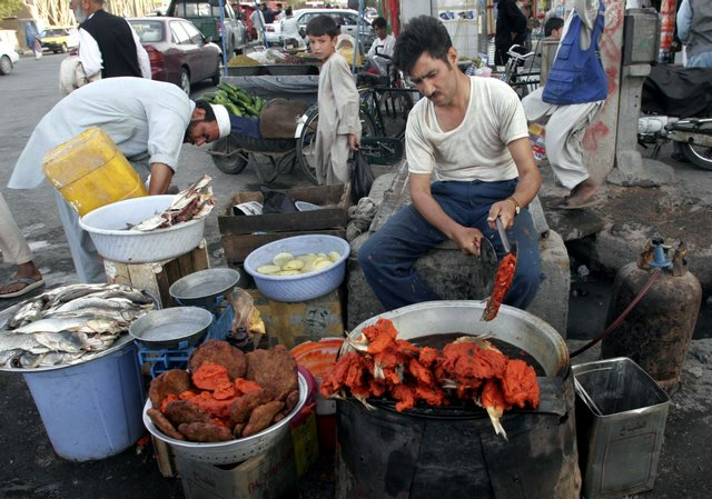 Photo An Afghan Street Vendor Fries Fish With Spicy