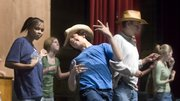 "Lawrence High School senior Andrew Connolly, who plays the role of country music star Garth Brooks, plays air guitar during rehearsal of ""The Jellybean Conspiracy"" at LHS. The play has a strong message about including individuals with disabilities in everyday life. Connolly has an onstage sidekick with developmental disabilities who plays the role of a Brooks admirer."