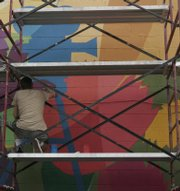 Jeremy Rockwell puts the finishing touches on a mural to honor black artists from Kansas.