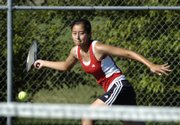 Lawrence High senior Yoshika Crider returns a volley during a tennis match against Blue Valley West High. The Lions were swept in the match Wednesday at Lawrence Tennis Center.