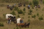 Riders and wagons travel a hillside, making their way as pioneers did in the 1800s.