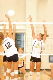 South freshman Alexis Scheibler, right, attempts a block against the Southwest Bulldogs during a freshman volleyball quadrangular Sept. 11 at Free State High. The Cougars met the Bulldogs in the title match of the quadrangular, but ultimately lost. Tonight, South gets another chance to take on the Bulldogs as well as Overland Park Aquinas.
