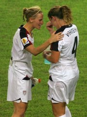 United States soccer players Kristine Lilly, left, and Cat Whitehill console each other after losing to Brazil. The Americans fell, 4-0, on Thursday in Hangzhou, China.