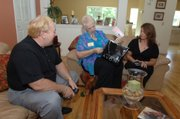 Avon advanced unit leaders Bobby McKinney, left, and his wife, Joy, deliver an order to Lya Delcid on June 23 at her home in Orlando, Fla. McKinney is one of a growing number of male salesmen supplementing their income selling products from the $9-billion-a-year beauty company. McKinney along with his wife did about $800,000 in sales last year. He has about 170 sales reps under him.