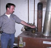 Jeffrey Ward explains rerouting the hot water pipes to run through his wood stove at his Farmington, Mo., home. After reading energy magazines about solar panels, he decided to install them. His efforts have begun generating more power than he needs, leading the city to purchase the surplus.