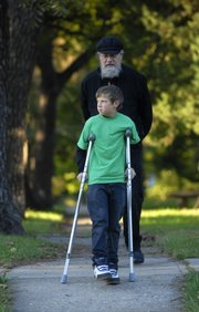 Cameron Reusch, a sixth grader at Cordley Elementary, hobbles to school with the support of crutches and his grandfather, Dan Rebik, on Monday, October 1, 2007.  Schools around the globe will celebrate International Walk Your Child to School Day on Wednesday. Reusch and Rebik walk to school everyday rain or shine.
