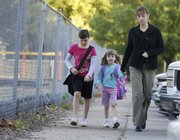 From left, Lexi Molzen, a Cordley School third-grader, her sister, Graci, a kindergartner, and their mother, Kerri, walk to school along Vermont Street. Parents and schoolchildren around the world will celebrate International Walk Your Child to School Day on Wednesday.