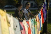 "Casey Pettit, left, a Kansas University senior from Topeka, and Nicole Tichenor, a KU junior from St. Louis, make their way along the Clothesline Project on Thursday at the Womyn Take Back the Night event at South Park. T-shirts decorated by survivors of rape or domestic violence or both were displayed publicly in the park and told their personal accounts with abuse.  ""Theres is so much violence happening everyday on a very personal level,"" Tichenor said."