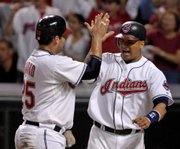 Cleveland's Victor Martinez, right, celebrates with Ryan Garko after both scored on Kenny Lofton's first-inning single. The Indians defeated the New York Yankees, 12-3, on Thursday night in Cleveland.